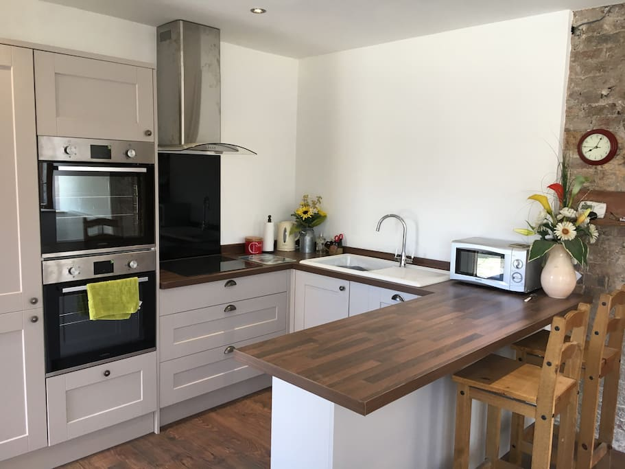 Modern open kitchen with breakfast bar, double oven, fridge, freezer, electric job, dishwasher and microwave