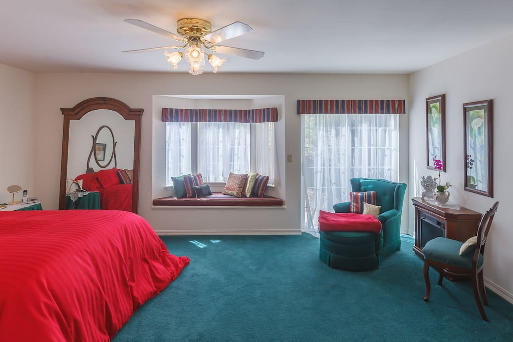 Large bedroom with queen sized bed.  TV in room.  Small refrigerator, microwave, coffee  maker, tea pot and toaster oven.