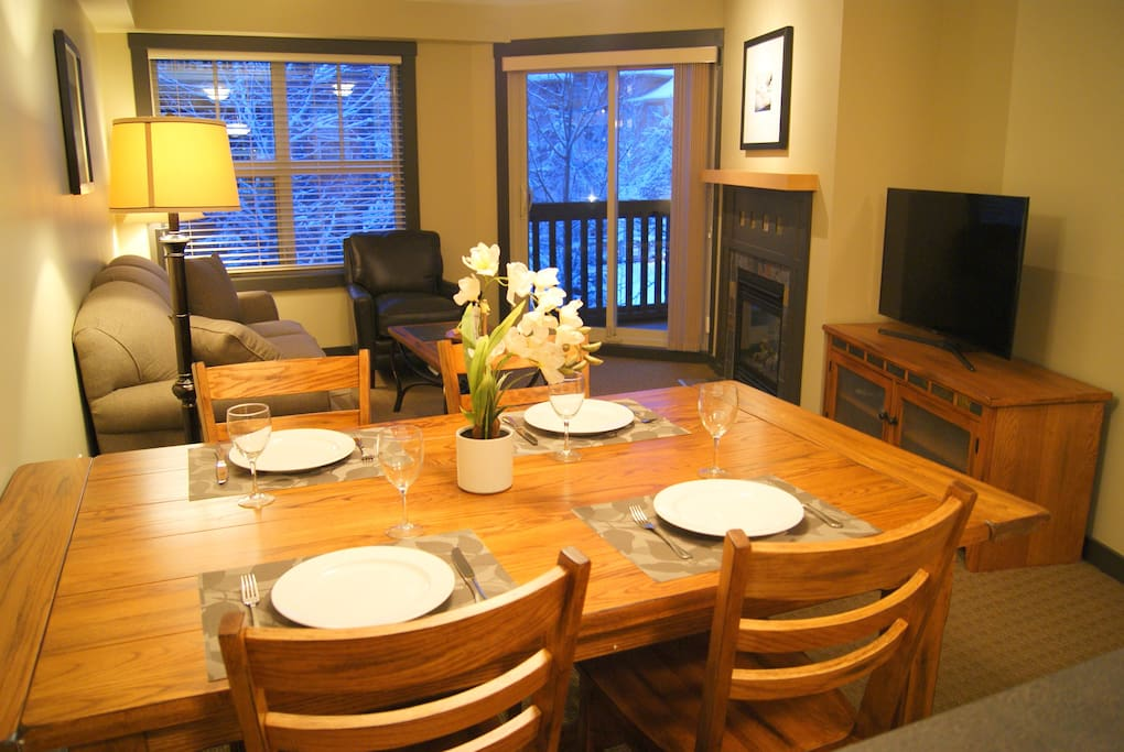 """Cozy living and dining room.  The couch converts to a Queen bed.  Gas fireplace, 40"""" TV, Wifi router in the unit."""