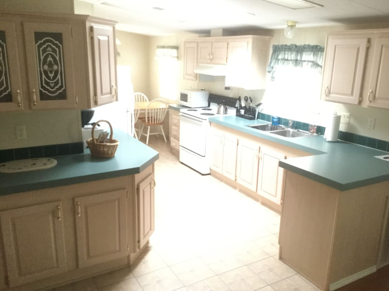Large open kitchen with dish set, refrigerator, electric stove, and microwave