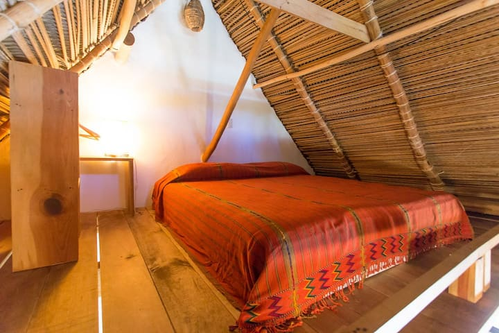 The king bed is upstairs in the loft. The thatched roof gives a rustic vibe. A large fan over the bed provides cool air.