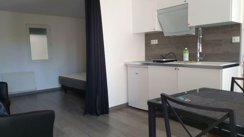 Espace cuisine et couchage séparées par un rideau occultant