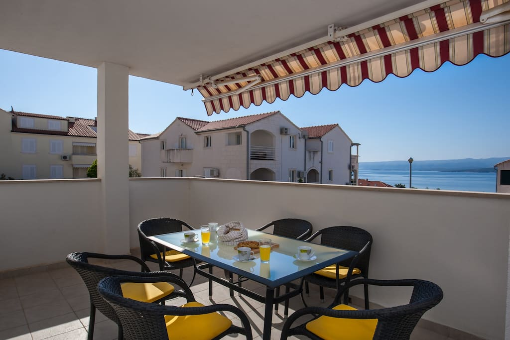 spacious terrace with dining table and sea&city view