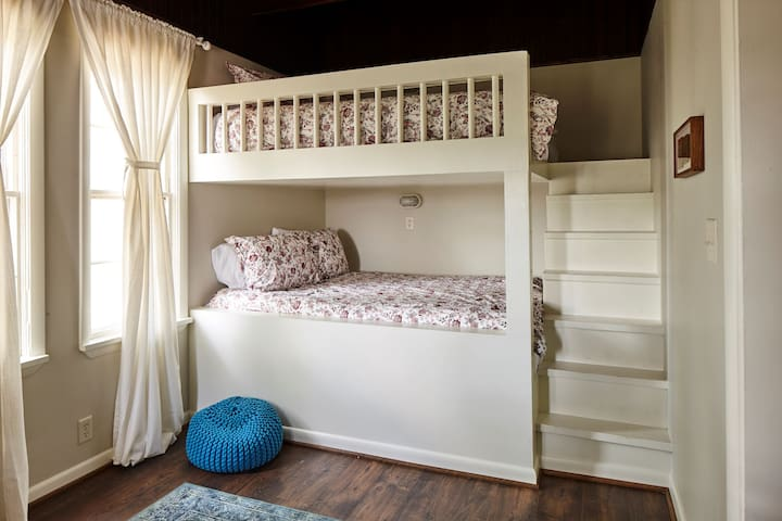 Built-in queen size bunk beds define the back bedroom. With four beds (two queens, a full, and a twin), this room can accommodate a large family or group. The former sun porch has now been enclosed, but we've restored its rich, dark oak ceiling.