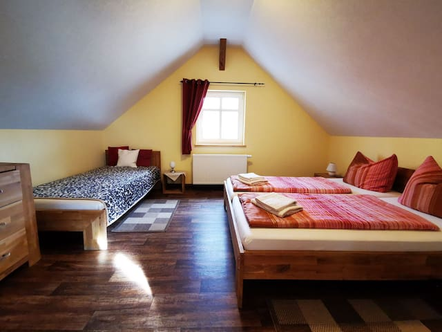 Schlafzimmer mit einem Doppelbett und einem Einzelbett im Obergeschoss