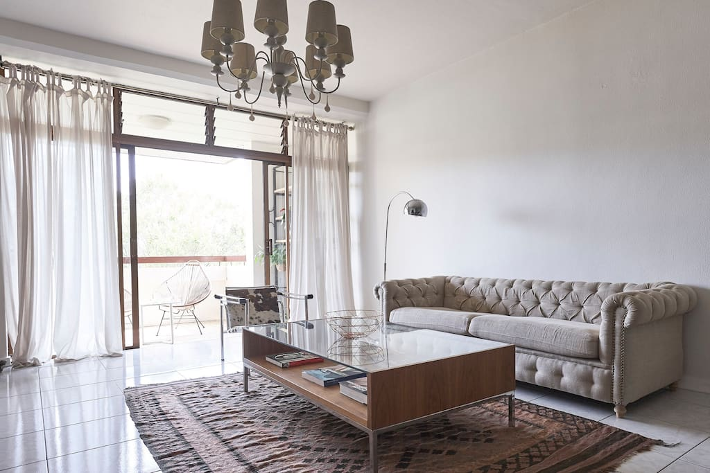 Lounge leading onto verandah looking at a beautiful garden below .