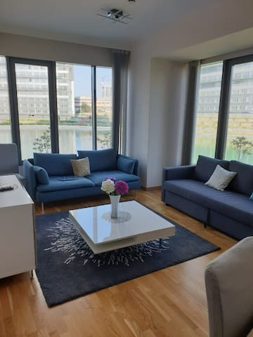 The living room is the heart of the home with beautiful large windows, stunning lake views, natural lighting, comfortable couches, a large SMART TV and a dining table against the far wall. Perfect for reading, relaxing, or socializing!