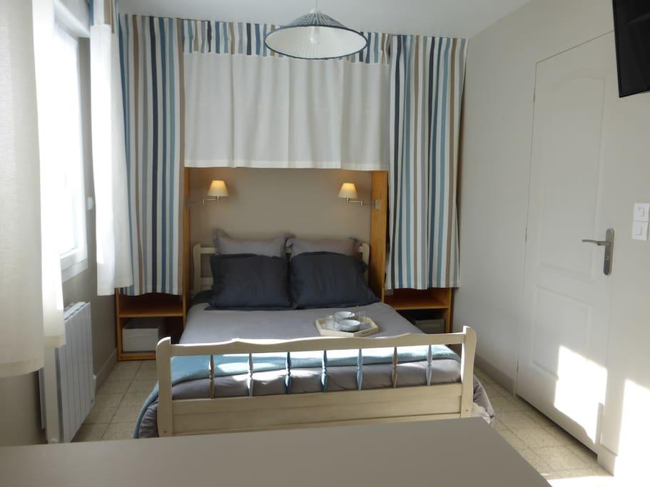 Coin chambre, lit éclairé par deux appliques, avec penderie de chaque côté du lit