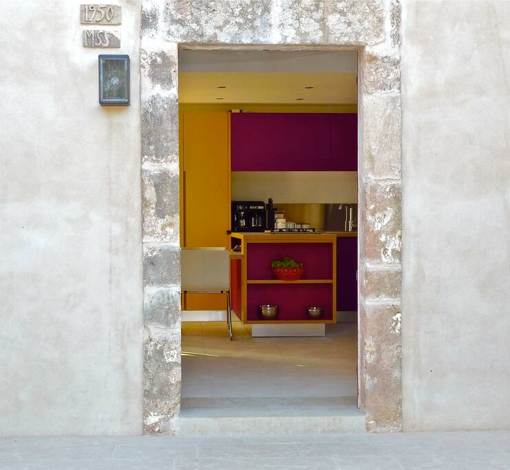 View through Casa Modesta's front door to the stunning bespoke kitchen in warm Moroccan inspired hues.