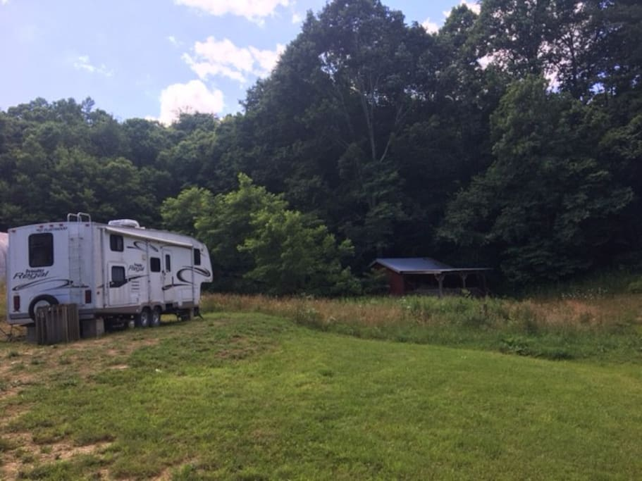 Large Regal Prowler RV is located on a grassy lot adjacent to forest and grassy field for children or dogs to play, or just to take a relaxing walk.