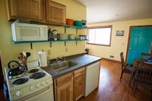Efficiency kitchen with cookware, utensils, and dishes