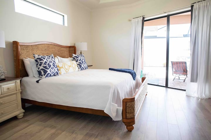 """Master suite with private access to the pool lanai for an early morning or late night swim.  Blockout blinds for privacy.  65"""" smart tv."""
