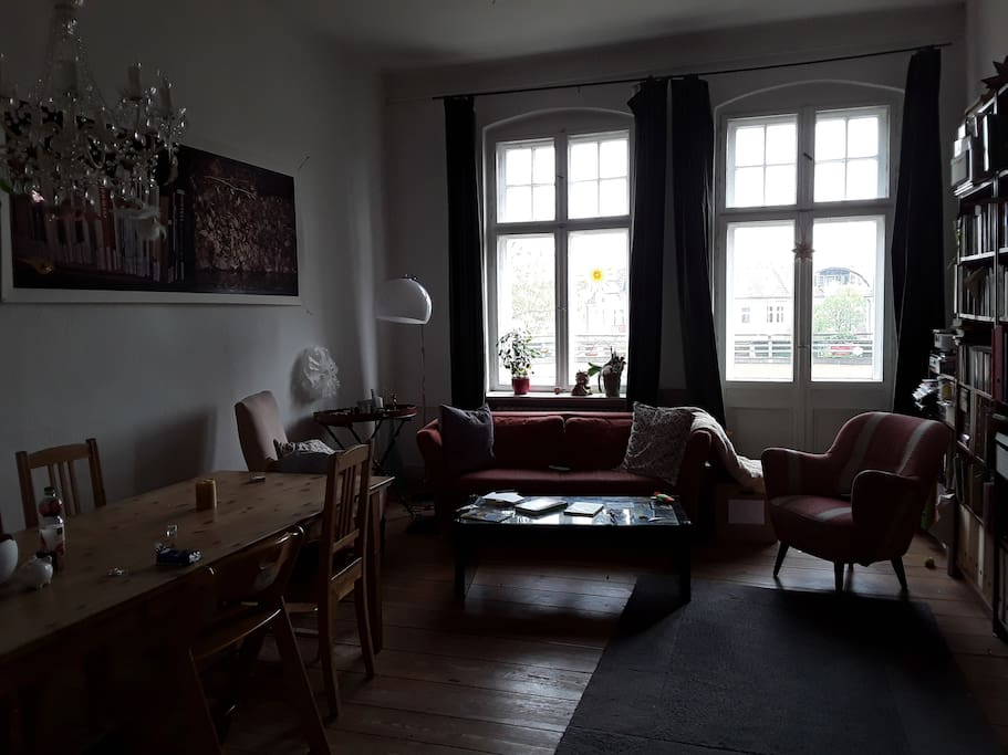 Großzügiges Wohnzimmer mit großem Esstisch und Schlafcouch