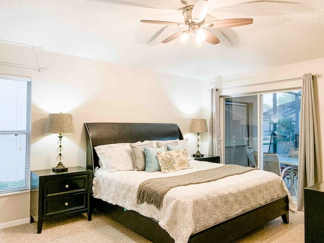 Luxury master bedroom with soft linens and private en-suite bathroom. Walkout to the covered patio and pool area. Smart TV and walk in closet.