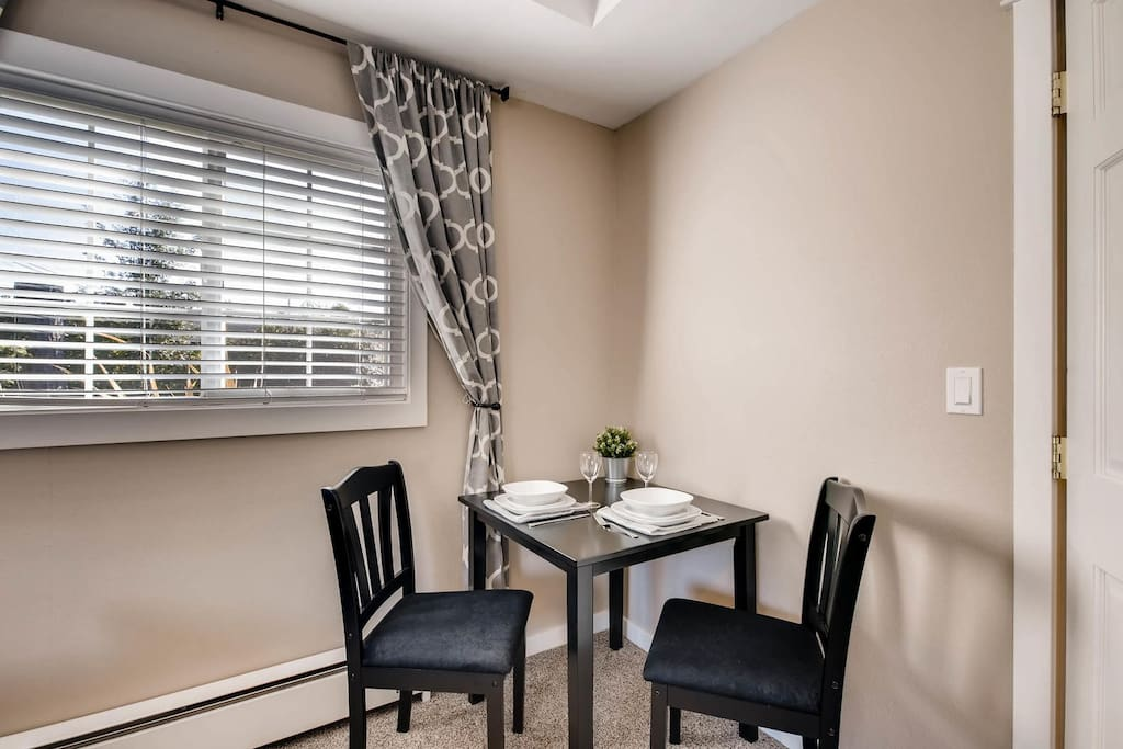 One corner of the room has a table for two that is perfect for dining.