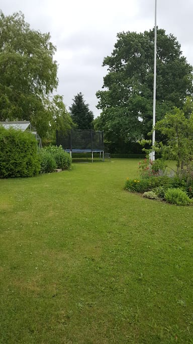 The garden with playground, trampoline  and greenhouse