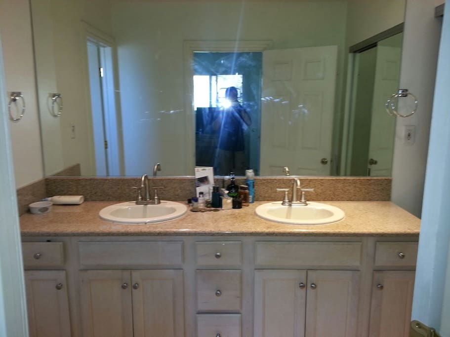 Dual bathroom sinks with large mirrors and recessed LED lights.   storage u