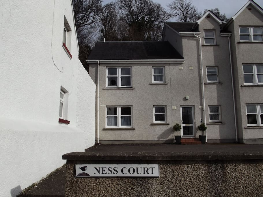External view of Ness Court showing the entrance door to the apartment with it's free parking space in front. This is a ground floor flat.