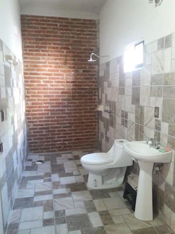 Baño con un toque rústico y fresco que da una pared de ladrillo expuesto. Agua caliente disponible.