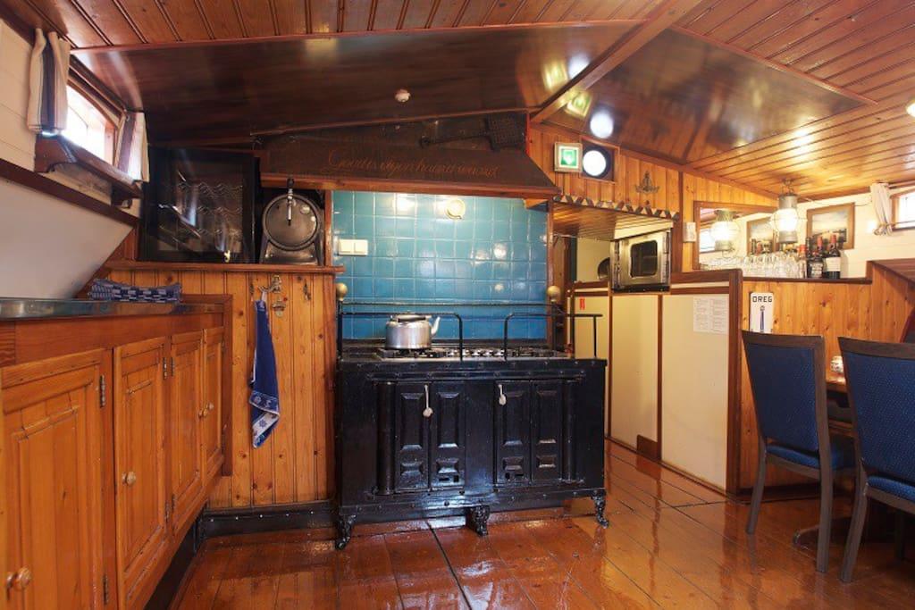 De keuken met fornuis en oven.