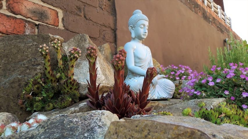"""Our garden rockery with """"TK"""" (our weathered Buddha in residence)"""