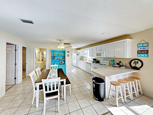 The well-equipped kitchen features quality all-white appliances and a 4-seat kitchen bar.