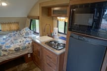 Full sized bed with comfy bedding, kitchen with sink, 2 burner stove, fridge freezer combo and microwave oven combo