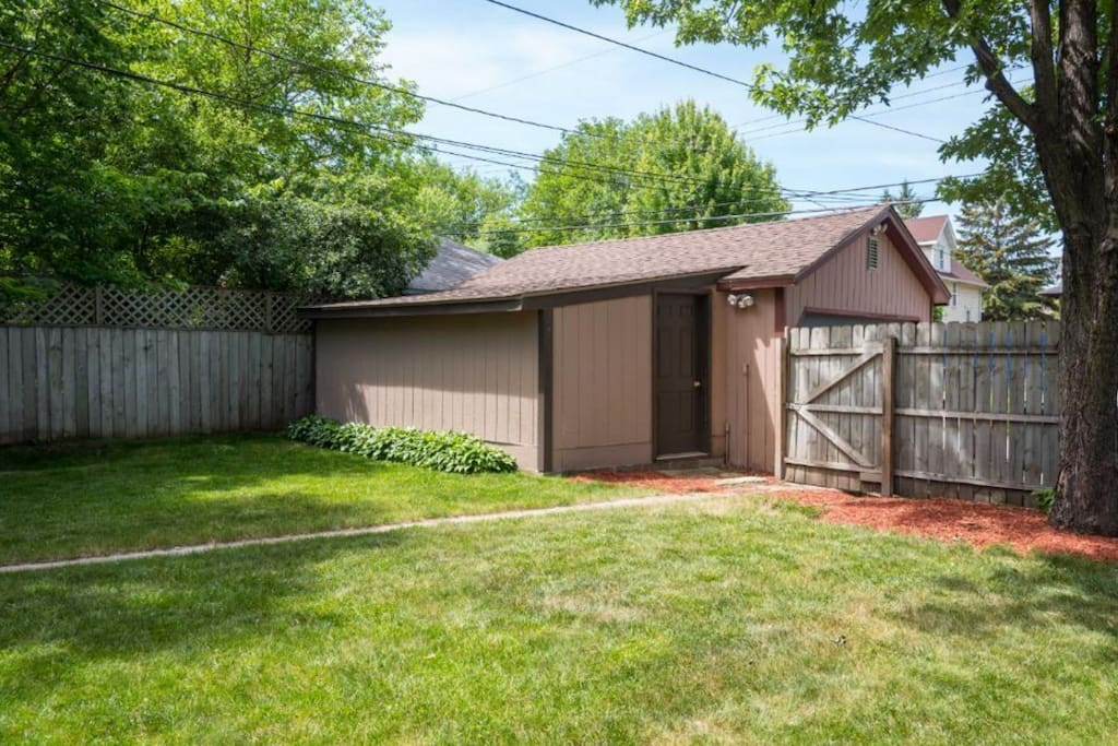 Large fenced-in yard with patio and detached garage.