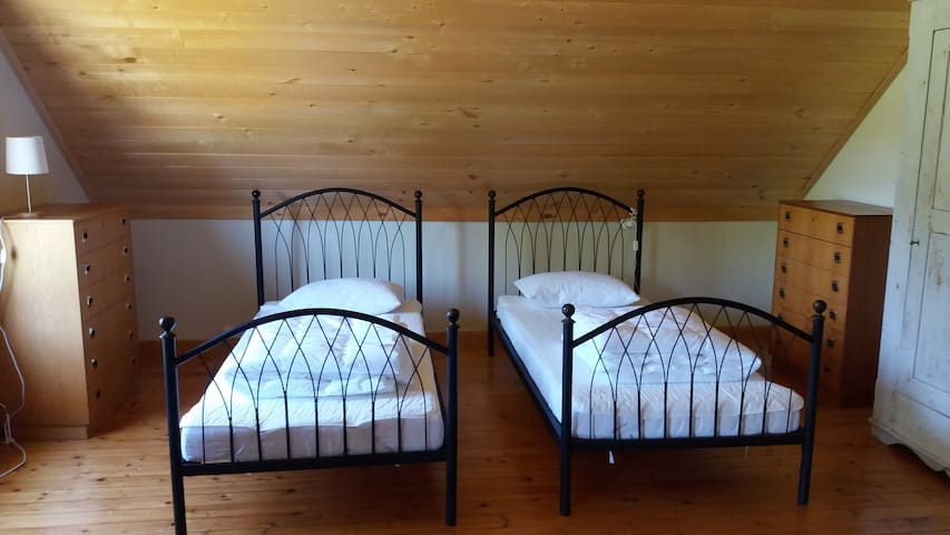 The upstairs bedroom has two single beds and a childrens cot.