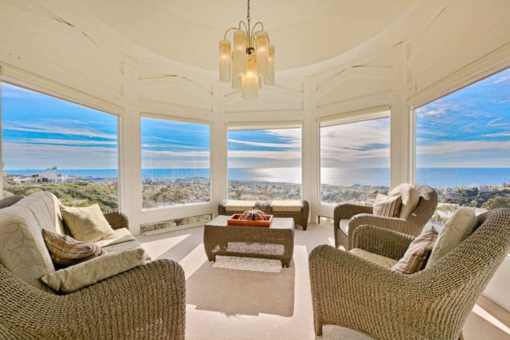 Seating Area with a fire pit showcasing sweeping ocean views and a city-light panorama at night.