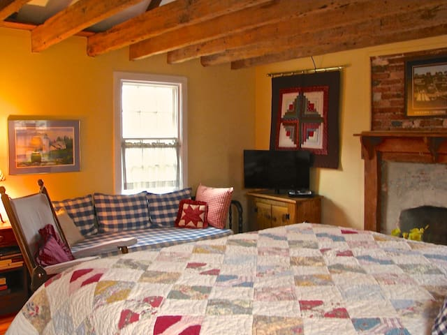 Bedroom with fireplace and ceiling fan, Hand hewn beams and cathedral ceiling