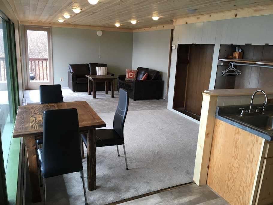 Living and dining areas, viewed from the kitchen. The entry into the apartment is from the outside deck, in the far left corner in this photo.