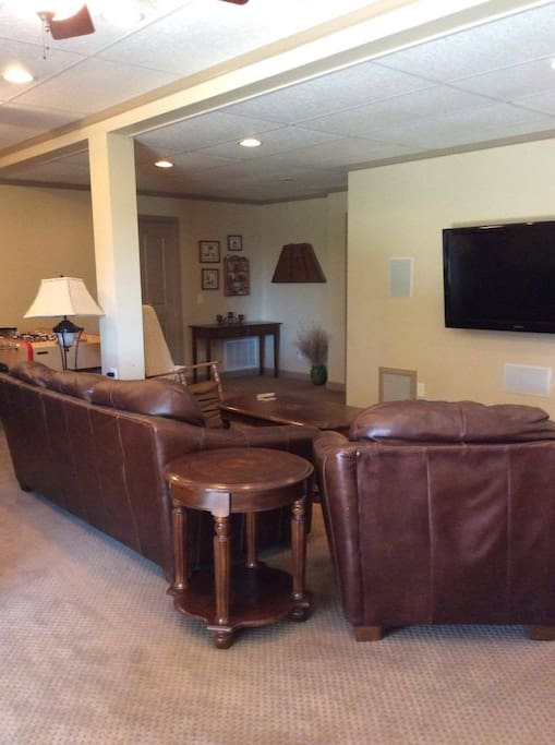 Flat screen TV and comfortable leather couches.