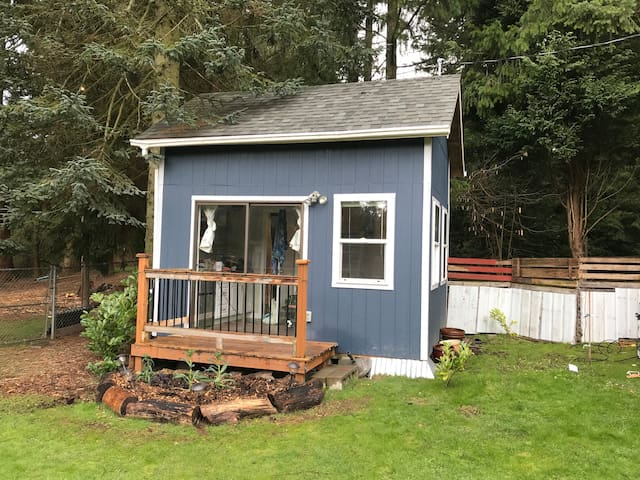 Rear of the tiny house with deck and small garden. Great when the sun is out.