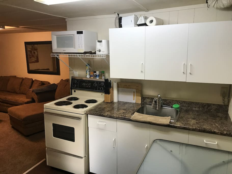 Kitchen area with stove, microwave, toaster, large fridge, dishes, cups, pots and accessories.
