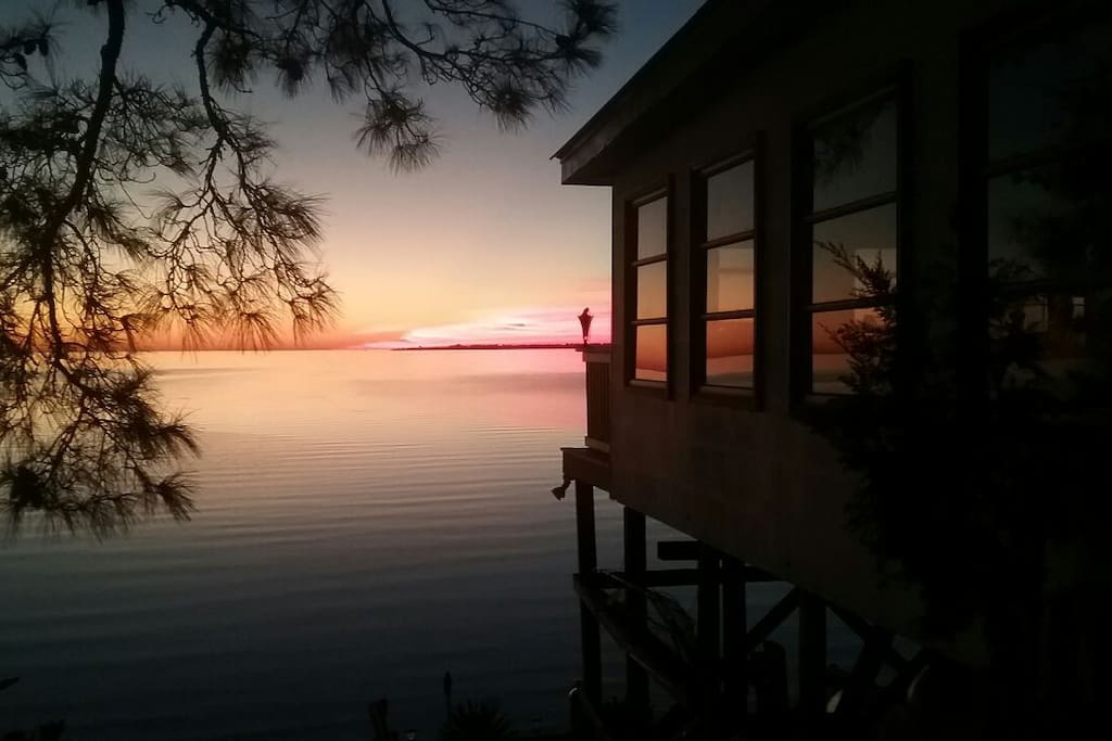 Taken from just beside the bungalow showing your view of the sun setting across the water .