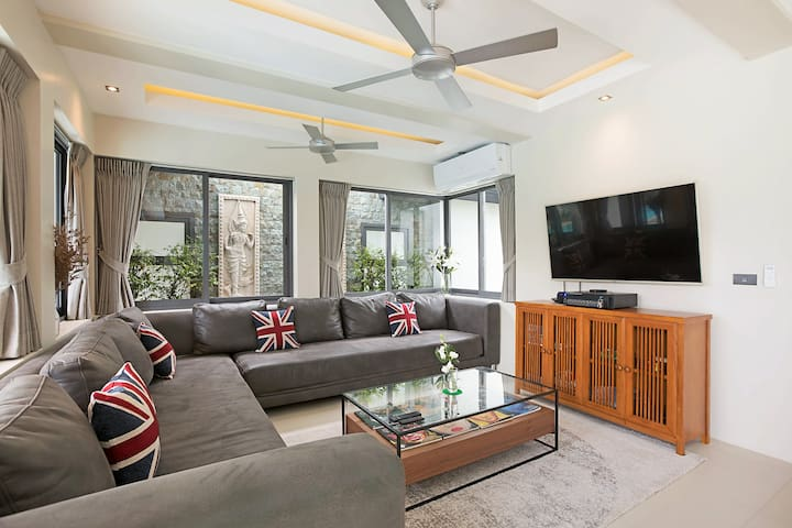 Living Room area with 65 inch TV and Pulse IPTV system showing all the sports plus movies and English TV channels, the room has air-conditioning and fans and an assortment of board games for the children