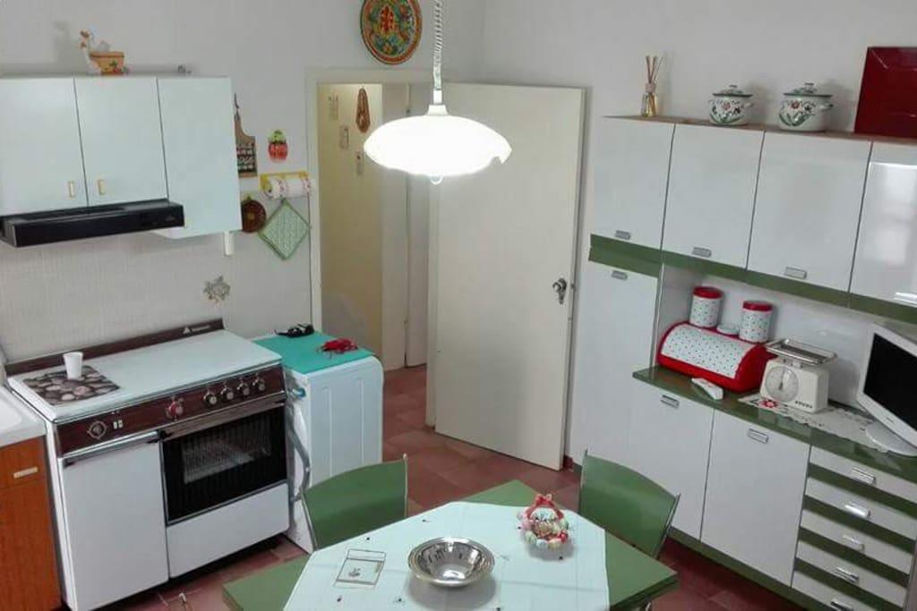 La cucina è fornita di: tavolo (estensibile) con 4 sedie, lavello, cucina con 4 fuochi a gas e forno elettrico, frigo con congelatore, fornetto a microonde, tv digitale, lavatrice, bollitore elettrico. Inoltre: piatti, bicchieri, tazze, tazzine, caffettiere, posateria.