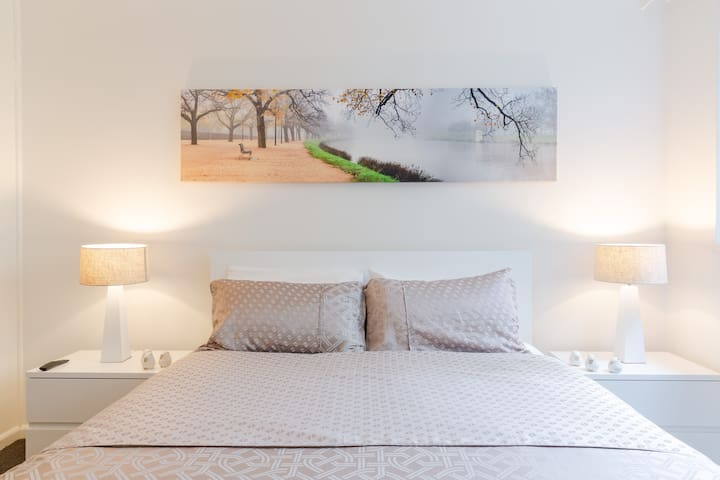 Your bedroom features a brand new queen bed and multi award winning mattress,  matching bedside tables and lamps, 2 phase block out blinds,   2 metre wide local artist original canvas photo of the neighbouring Yarra River and double glazed windows.