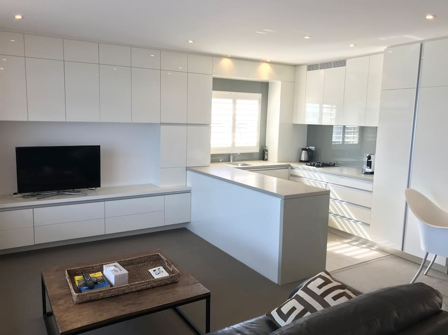 Stylish furniture and very sunny living room with open plan kitchen.