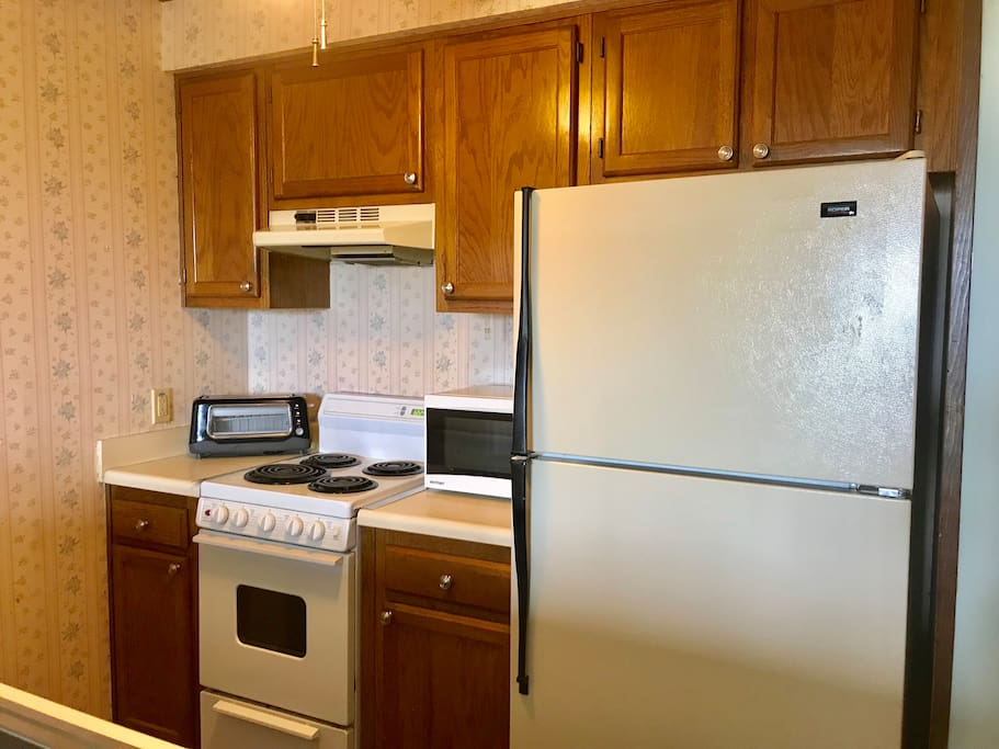 Full Kitchen with ceiling fan, dishwasher, coffee pot, toaster, microwave, small oven and 4-burner electric stove top.
