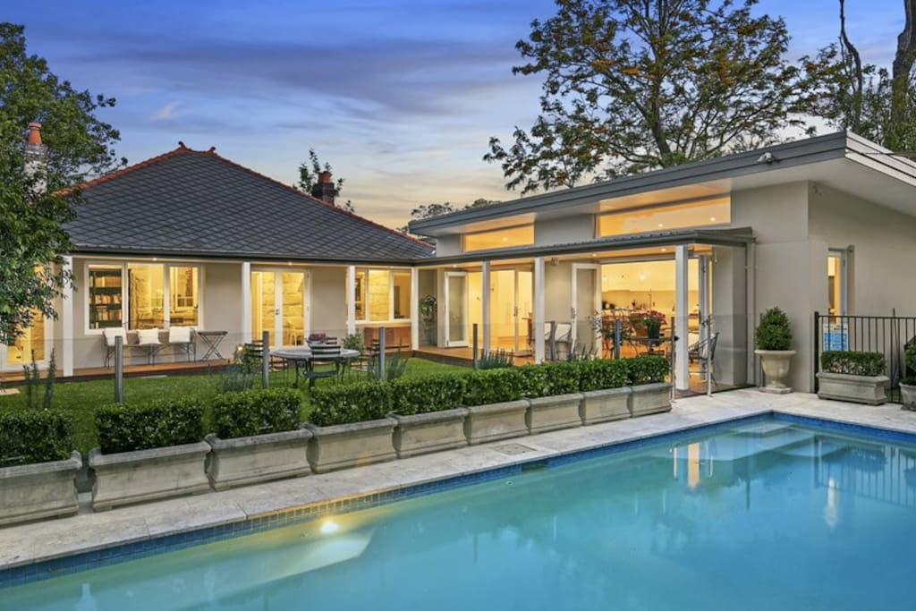 10m pool, safely surrounded by a glass fence, with sun lounges and outdoor shower.