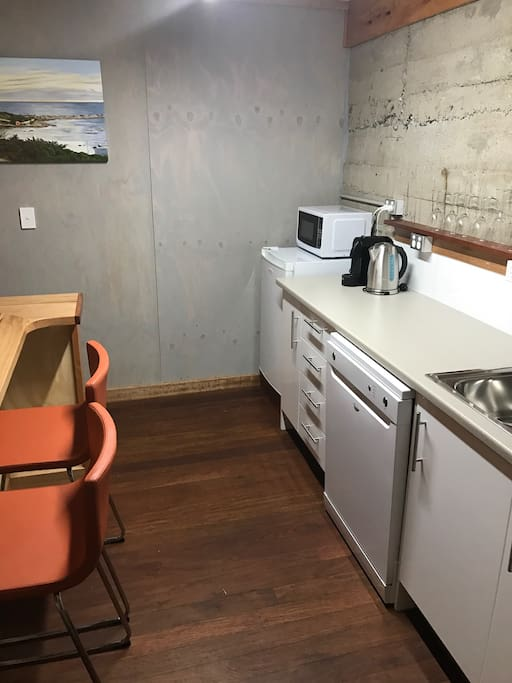 Modern kitchenette with dishwasher, coffee machine, toaster, kettle, microwave and induction cooktop etc.