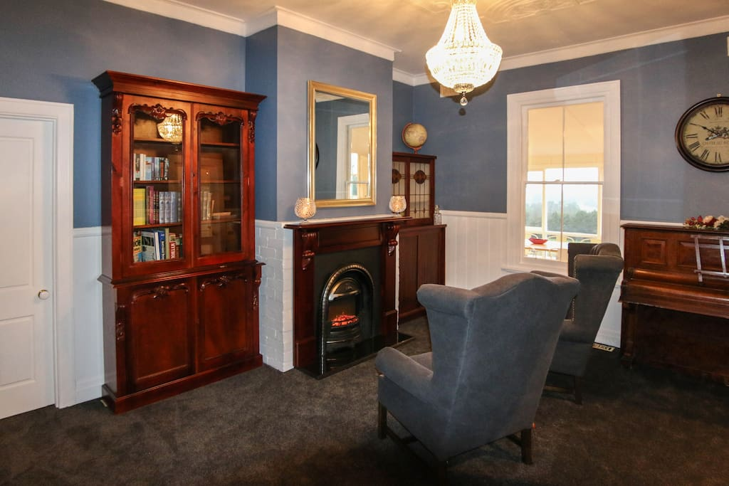 Sitting Room with piano, liabrary and electric fireplace