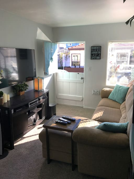 """TV/Living area.  Comfortable couch with chase.  55"""" HD TV, Bose Surround Sound, IPod/Phone dock for music, Wifi."""