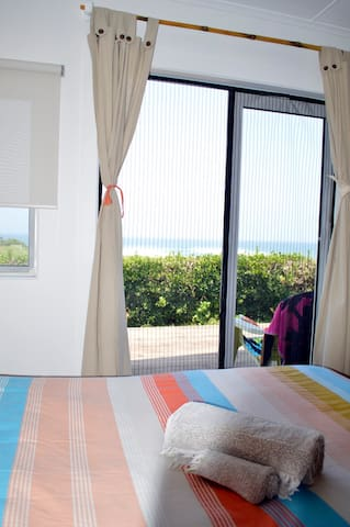 Bedroom 1 with queen bed and ocean views. Fly screen on the French doors so you can leave open during the day.