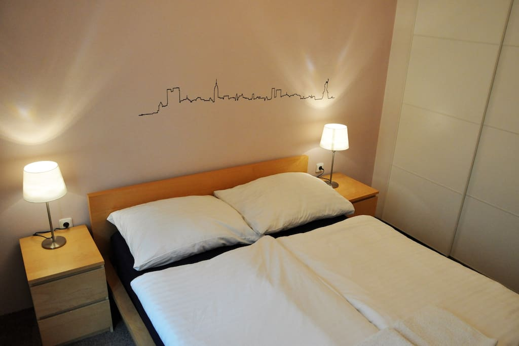 The bedroom has a classical double bed and bedside tables with lamps.