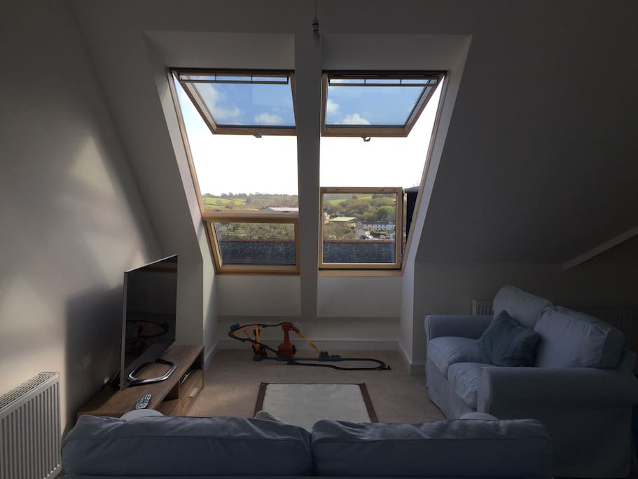 Living room with large velux Windows; one of which opens out into velux balcony. Penthouse is light and airy with excellent views