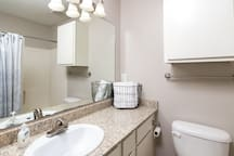 Bathroom with counter space and full size bathtub with shower
