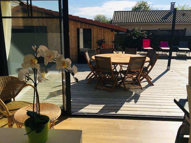 Grand Terrasse orientée sud en bois devant le séjour avec grande table 8 place, transat, et petite table métalique.